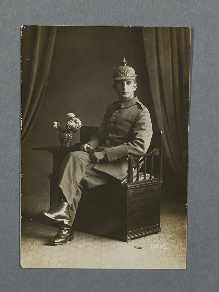 Black and white image of a man in German army uniform with a spiked helmet sitting on a bench next to small table with flowers.