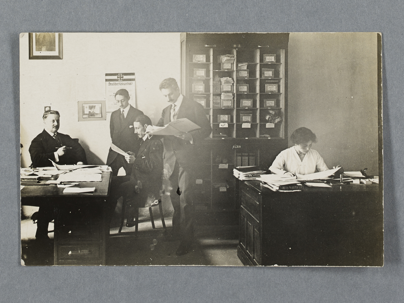 Black and white image showing Eva Ehrenberg working on a desk and three male colleagues on the opposite side of the office