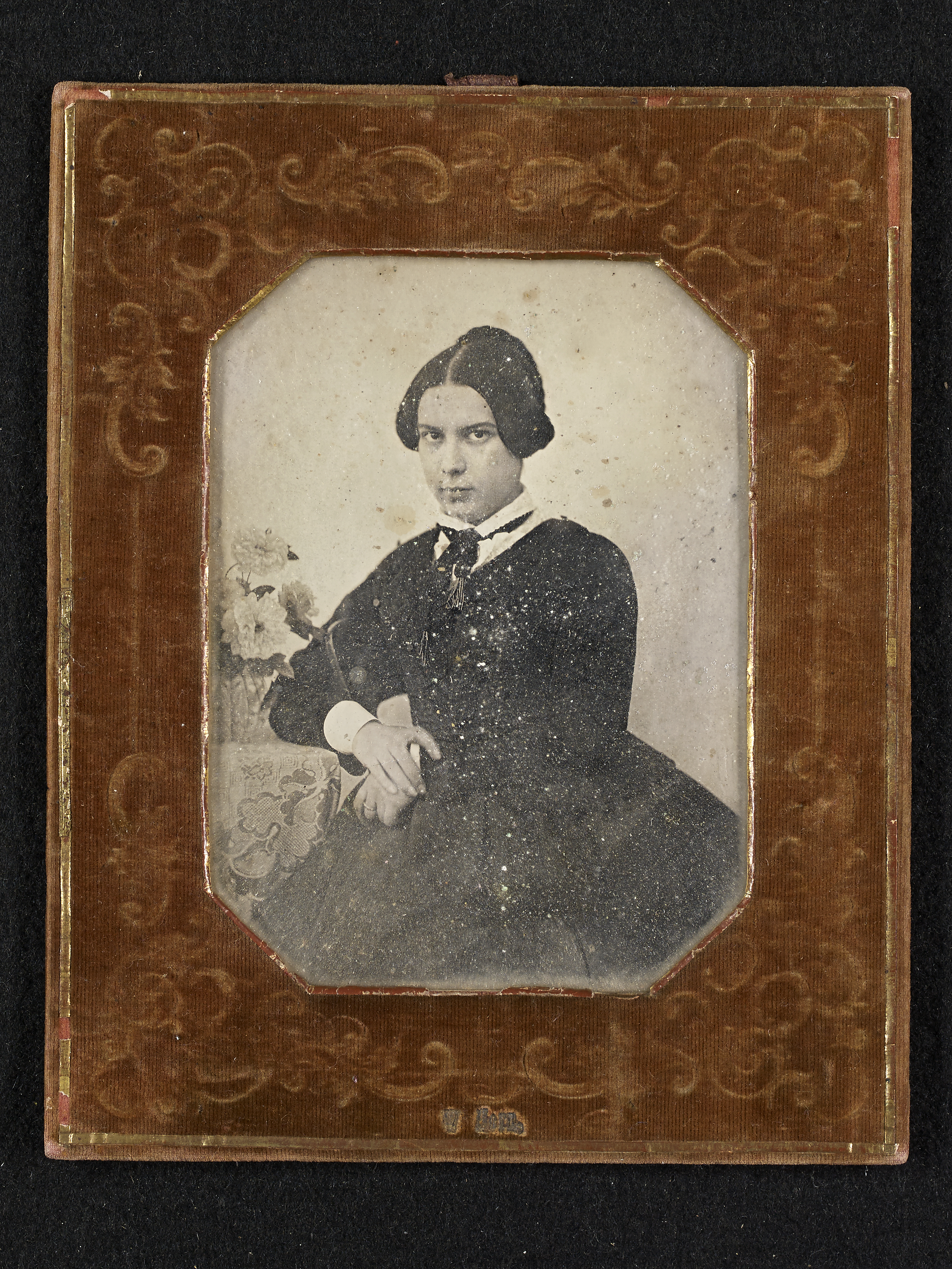 Black and white image of a young woman in a brown photo frame