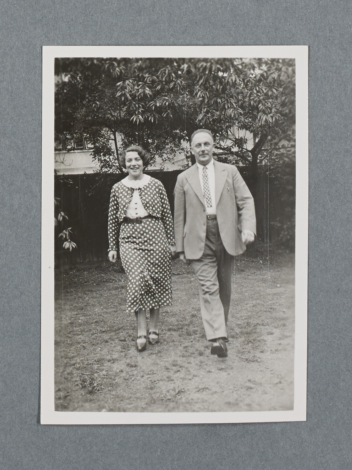 Black and white photo of a young woman and a middle aged man walking towards the camera, both smiling