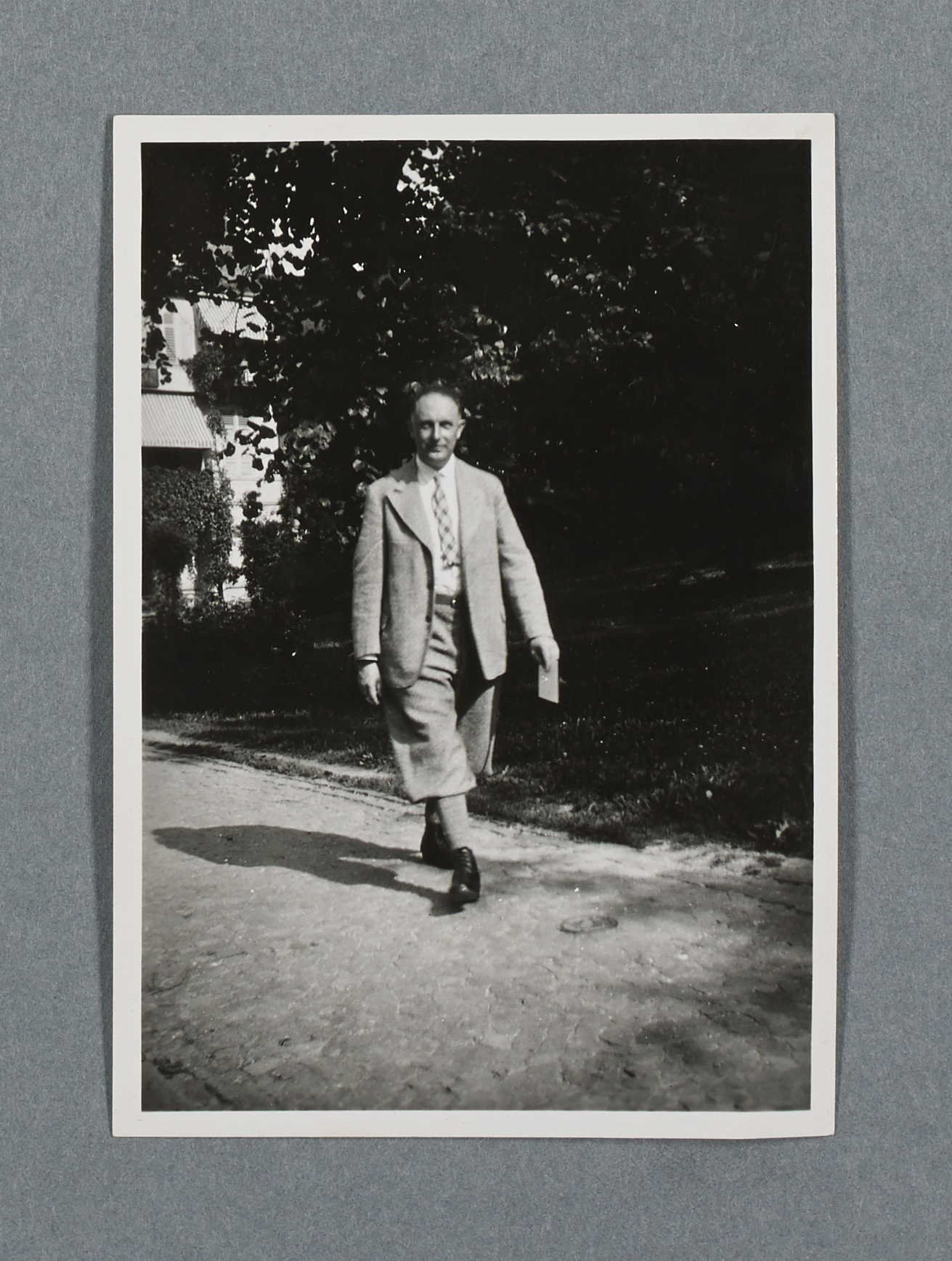 Black and white image of a man holding a card, walking towards the camera