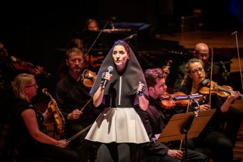 Music artist Gazelle Twin stands in a spotlight on stage holding a mic, wearing a black hooded cape and grey skirt. Behind her, dimly lit, are members of a string orchestra.