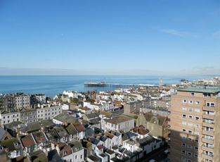 The Brighton skyline, showing many different types of houses and flats, and looking out to the sea in the distance.