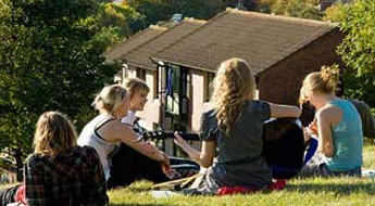 A group of students sat on the grass beside Brighthelm halls on Sussex campus
