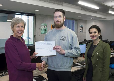 William Jobson Pargeter, winner of the financial trading competition, receives his certificate from Sue Newell and Madina Tash