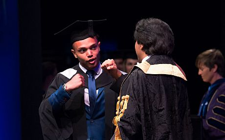 A graduand and Sanjeev celebrating on stage