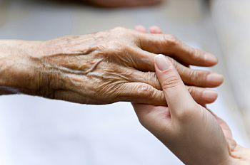 An elderly persons' hand being held by a younger person