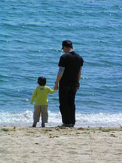 A photo of a father with his child, standing on a beach holding hands and looking out to sea