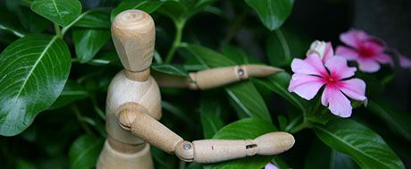 wooden mannequin in leaves and flowers