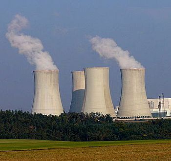A photo of a nuclear power plant, its towers steaming