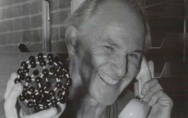 Sir Harry Kroto holding a model of a Buckyball whilst talking on the telephone.