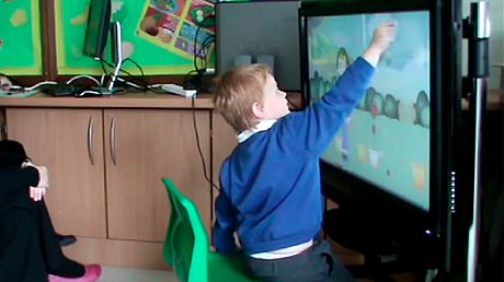 An autistic red hair child is touching a screen.
