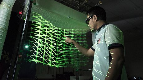 Person interacting with a futuristic interface that is green and emitting light.