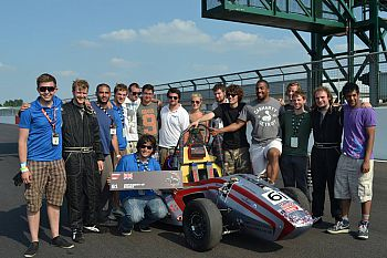 Formula Student Team pose with car on a race track.