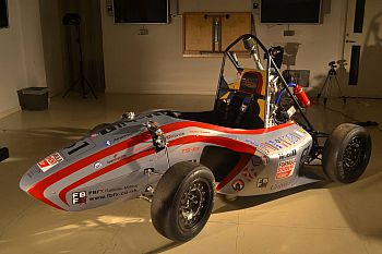 Photo of the formula student car in a brightly lit studio.