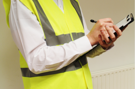 A photo of a person wearing a hi-viz vest with a clipboard