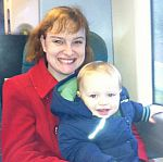 Jessica sits with her son on a train