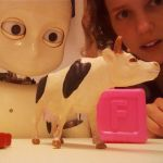 A robot looking at a toy cow and a toy block while Katherine Twomey looks on from behind.
