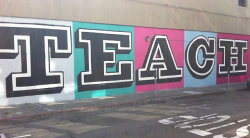 "The word ""teach"" graffitied on wall"