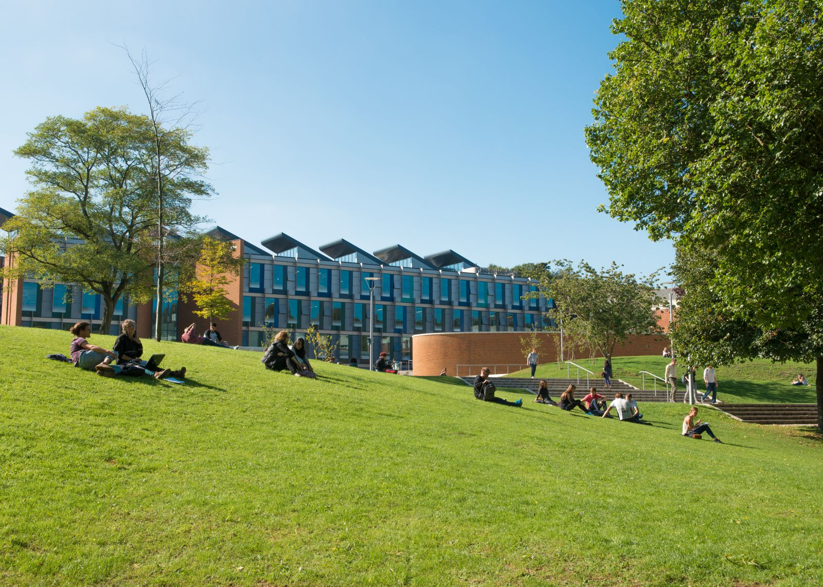 Business, Management and Economics students studying on the grass outside their academic building