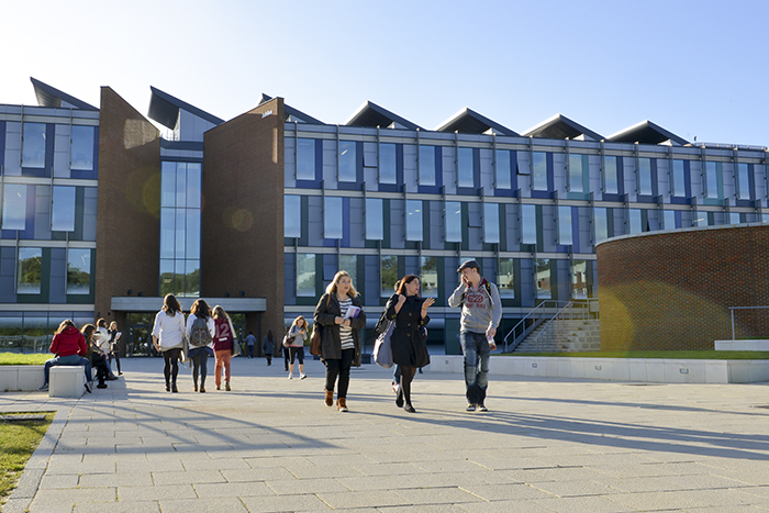 Masters students walking on path close to the Jubilee building on the University of Sussex campus