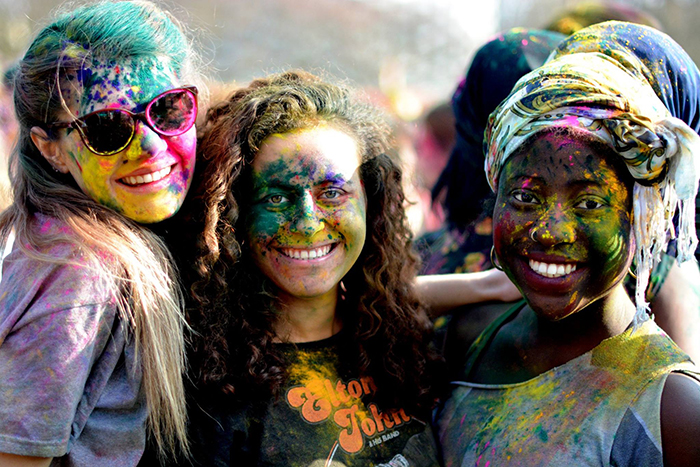 Three international Sussex students celebrating Holi as part of our One World Week