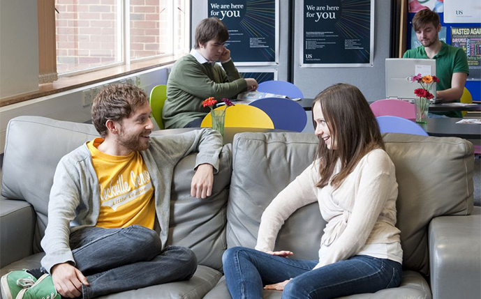 Two students talking on the sofa in the Student Life Centre, with Sussex signs in the background that read We are here for you