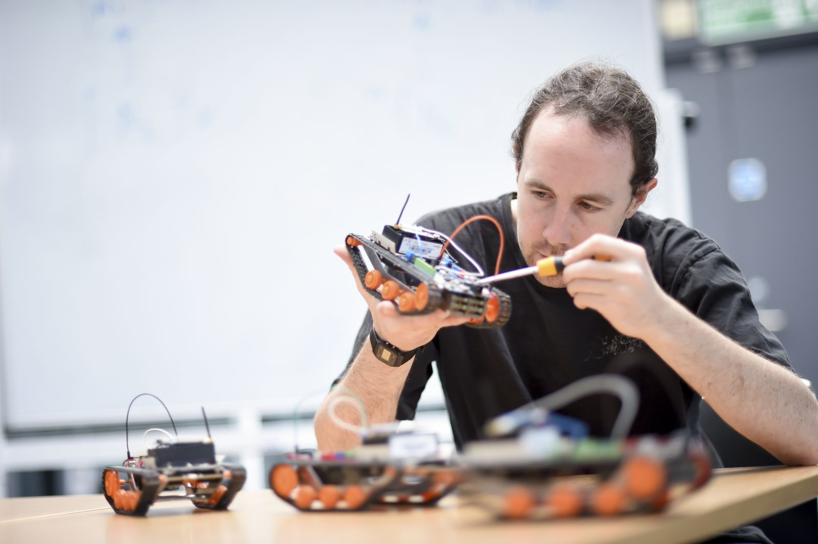 A PhD student works on mini-robots for his robotics project at the University of Sussex