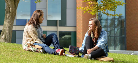 PhD students sitting on the grass outside the Jubilee building, where the School of Business, Management and Economics is based