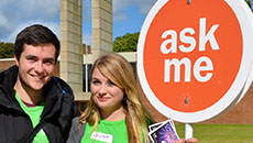 Two student helpers at a masters open day, holding a sign that says ask me