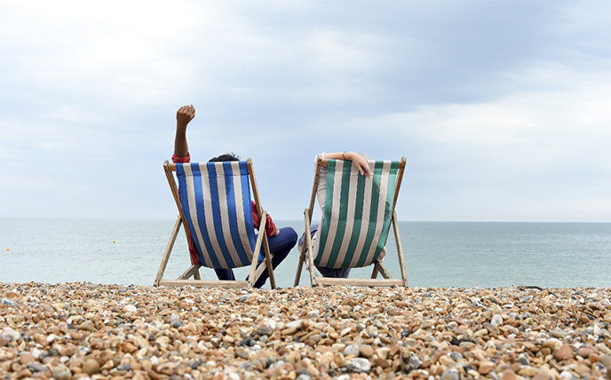 Students in deckchairs on Brighton beach