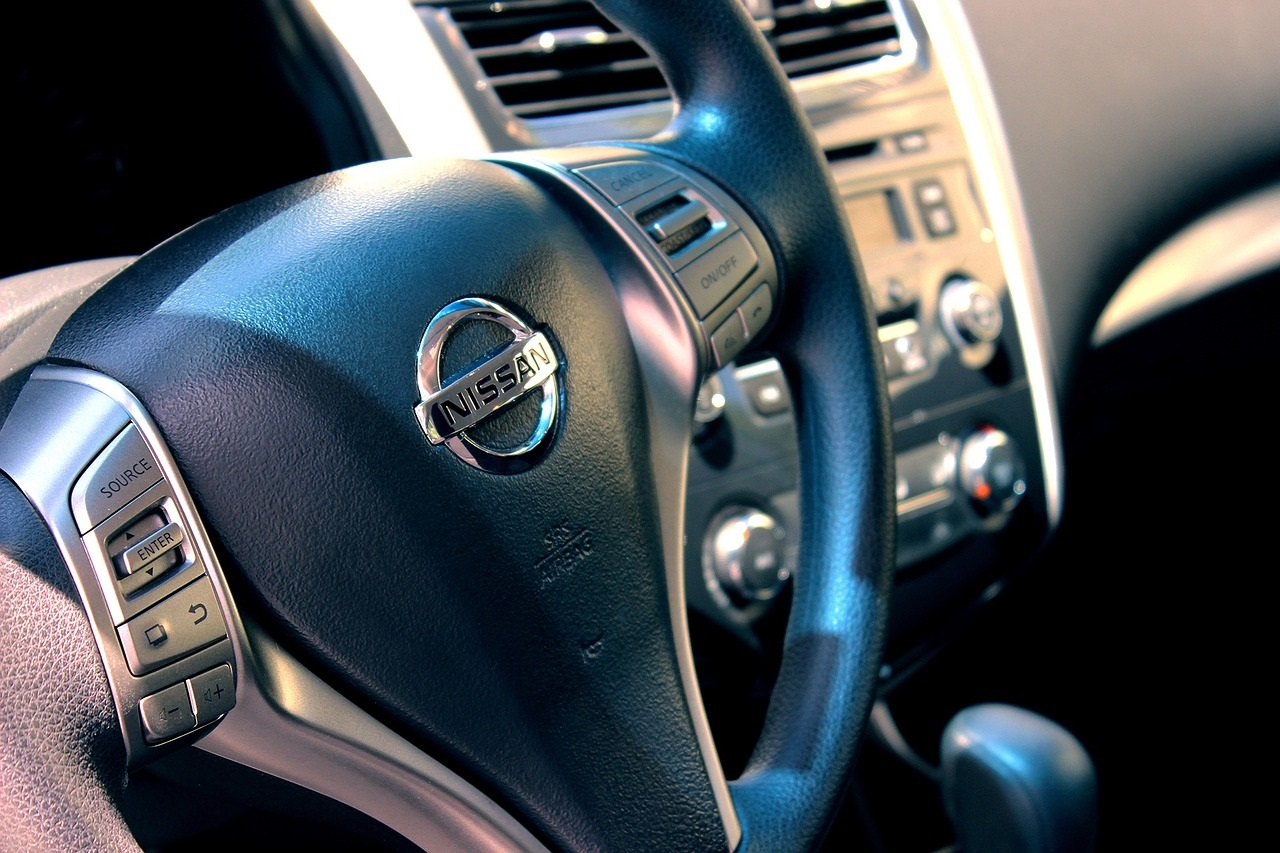 A close-up photo of the steering wheel of a Nissan car