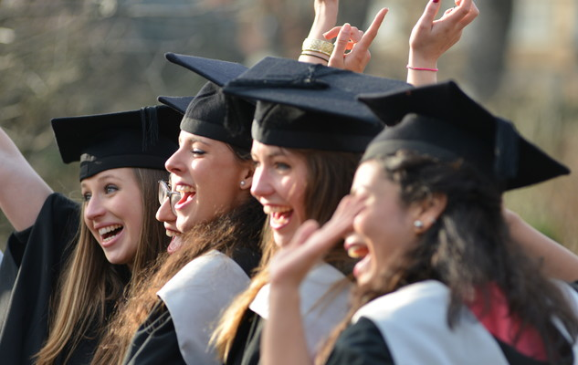 A group of female students celebrating at a graduation ceremony