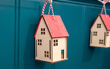Two trinket models of houses hanging on string to represent the importance of neighbourliness
