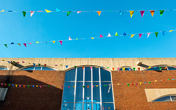 Part of a campus building against a blue sky with bunting fluttering in the wind