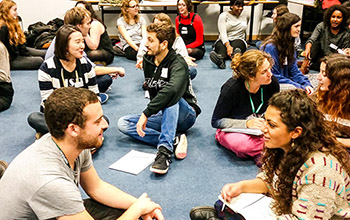 A group of students sat on the floor of a meeting room in discussion as part of a community session