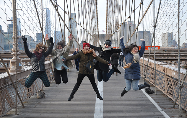 Students jumping on a bridge in New York during their study abroad year organised by the University of Sussex
