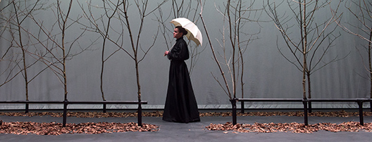 An actor holding a white umbrella walks across a dark stage lined with trees.