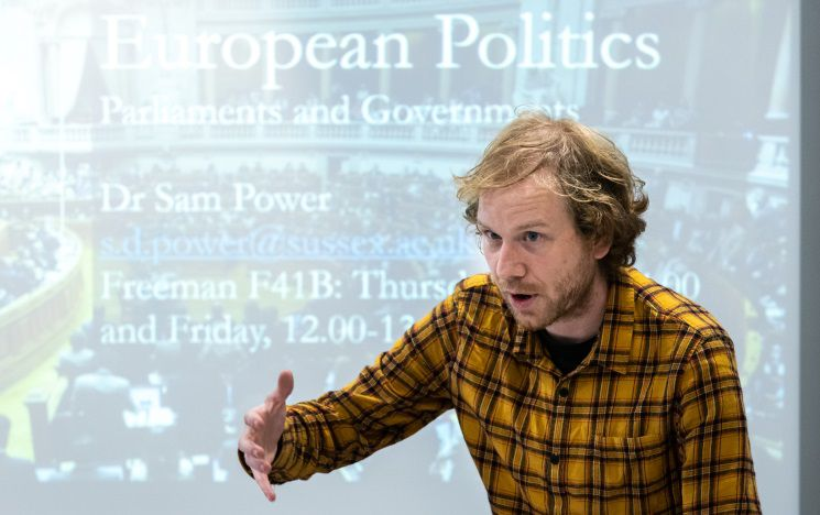 Lecturer Sam Power giving a lecture in front of a smartboard