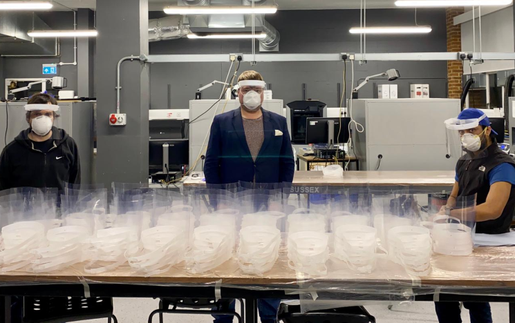 Three engineers pose with a table with hundreds of face masks