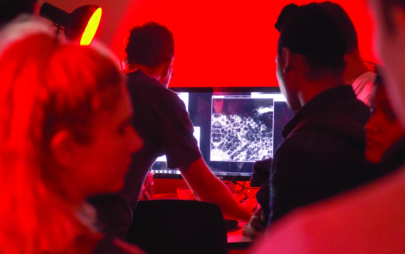 Neuroscience students looking at neural data on a computer monitor