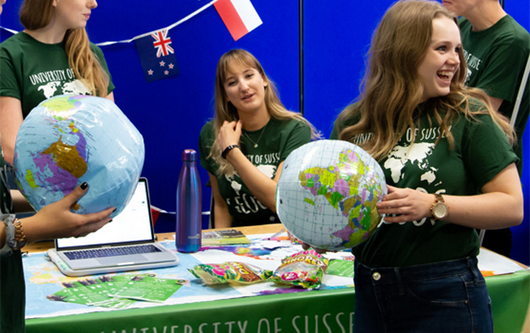 Four members of Geography Society at a fayre table smiling