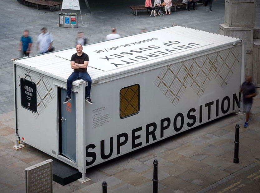 Professor Winfried Hensinger sitting atop a Quantum Technology research display portacabin emblazoned with 'Superposition'