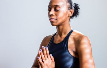 A woman wearing workout clothes sits in a yoga pose, with her eyes closed and her hands pressed together