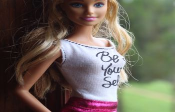 A Barbie doll stands by a window wearing a pink skirt and white top with the text Be Your Self written on it
