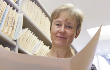 Professor Val Jenkins facing the camera and holding a file