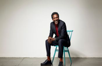Lemn Sissay MBE is photographed sitting on a white chair in a studio. He is dressed smartly in a jacket and smiling at the camera