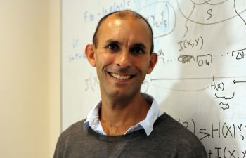 Professor Anil Seth stands in front of a white board with mathematical equations written in black pen wearing a grey jumper and blue shirt