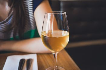 A close up shot of a glass of white wine with a woman wearing a blue and white stripey top in the background sitting at a restaurant table