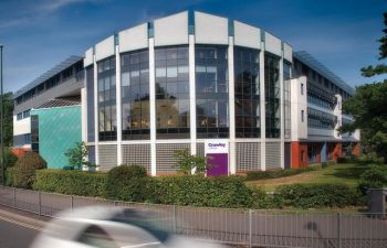 A view across the road of Crawley College - a modern looking glass fronted building set behind a small hedgerow